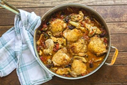 One-Pan Low FODMAP Chicken, Artichokes & Olives in pan on wooden surface