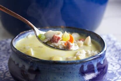 closeup of low FODMAP fish chowder on spoon and in rustic blue bowl