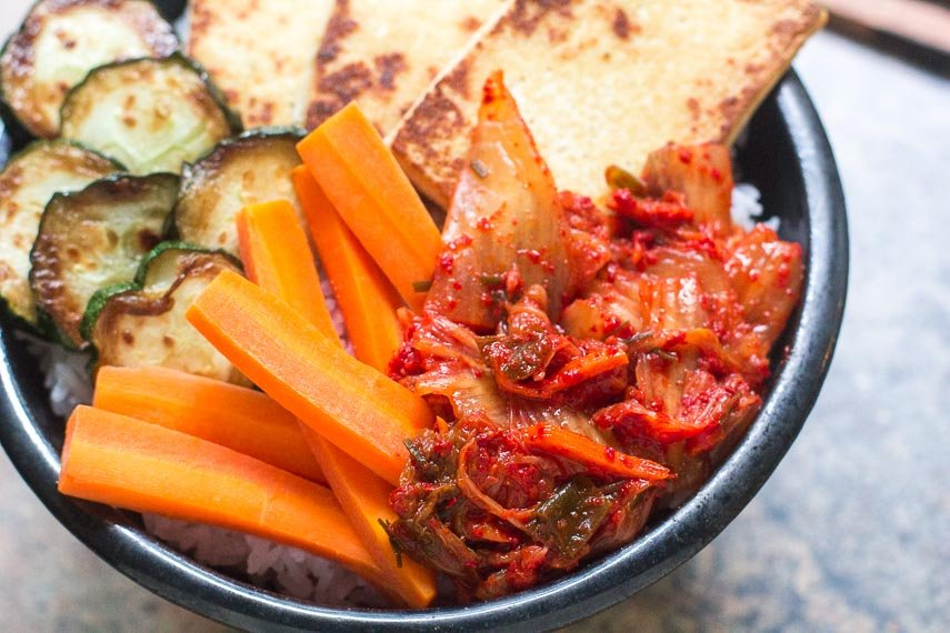 closeup of low FODMAP kimchi in bowl with tofu, carrots and zucchini