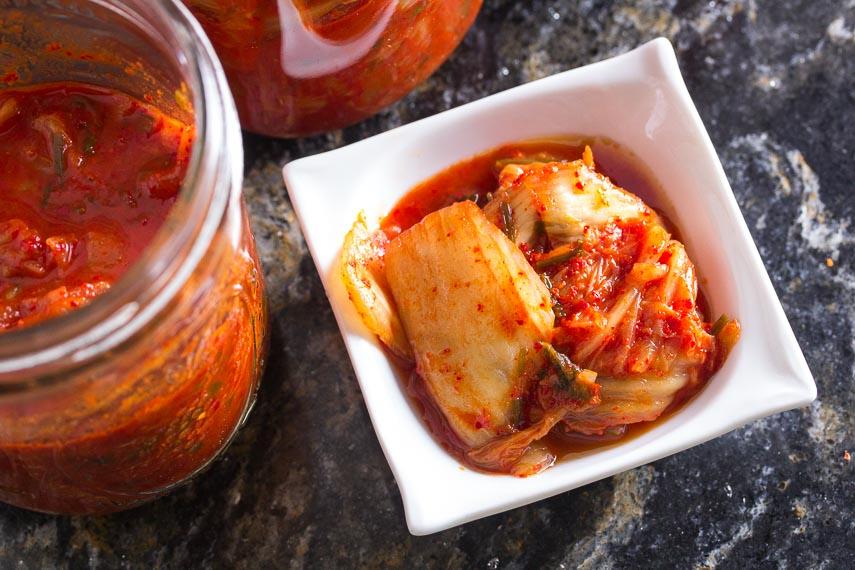 closeup of low FODMAP kimchi in small white dish on dark quartz counter