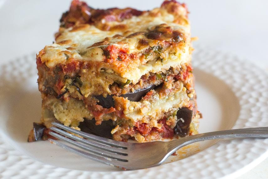 closeup of slice of low FODMAP Eggplant Parmesan on white plate with fork