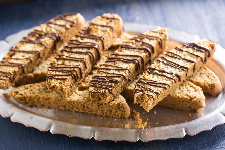 closeup on chocolate drizzled low FODMAP Ginger Biscotti on silver platter