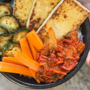 hands holding bowl of rice, tofu, zucchini, carrot and low FODMAP kimchi