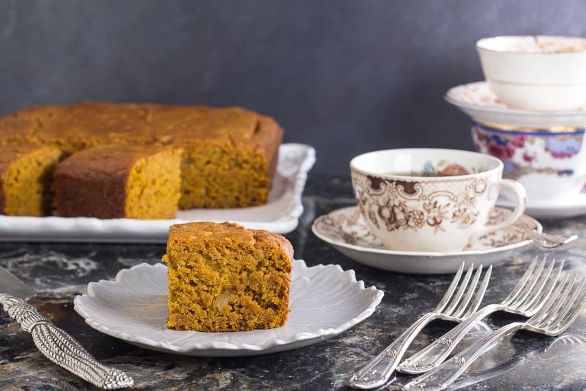 low FODMAP Triple Ginger Pumpkin Cake on decorative plate; silver folks and teacups alongside
