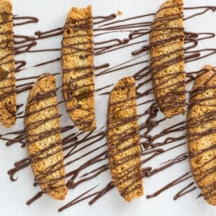 low FODMAP triple ginger biscotti drizzled with chocolate on parchment lined pan