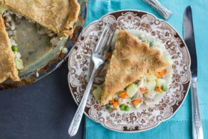 overhead image of Low FODMAP CHicken Pot Pie slice on brown decorative plate on teal cloth; whole pie alongside