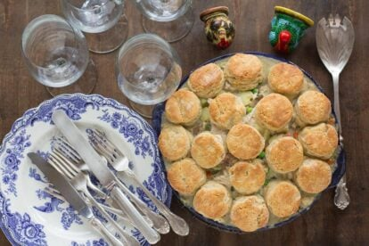 overhead image of Low FODMAP Leftover Turkey Pot Pie with Biscuit Topping on brown wooden background; blue and white plates alongside