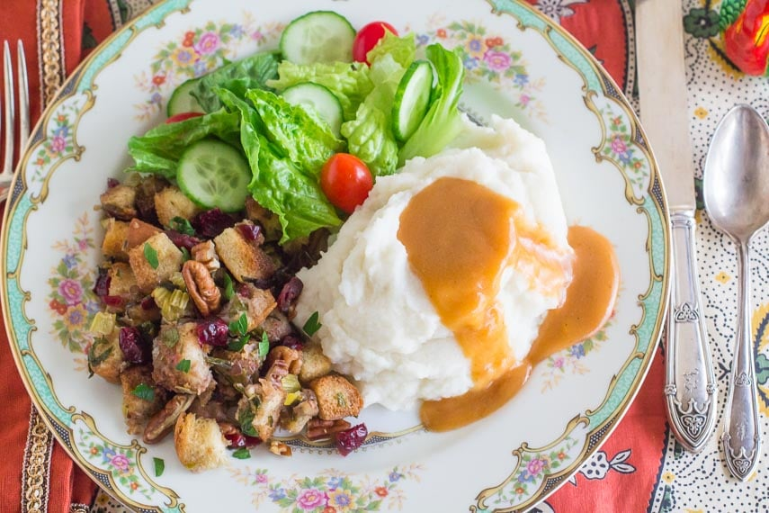 overhead of Low FODMAP vegetarian gravy on mashed potatoes with stuffing and salad on decorative plate