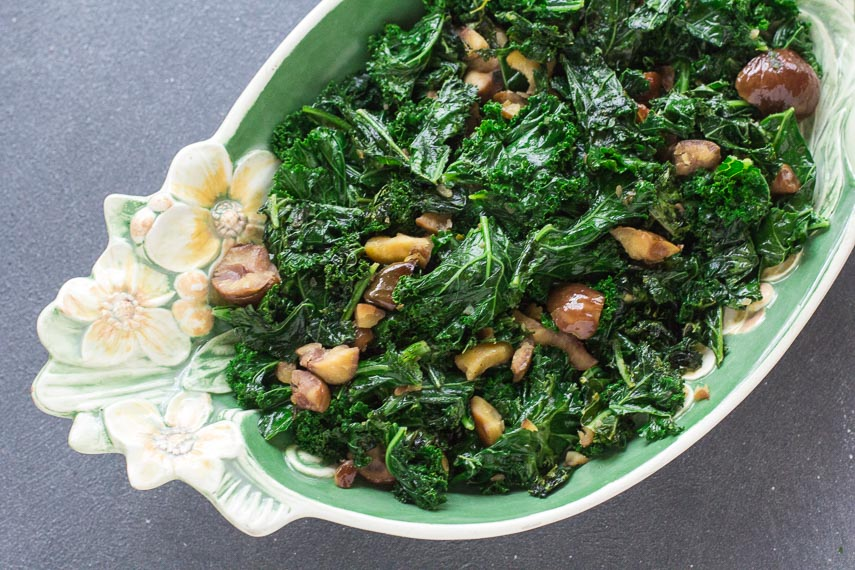 overhead view of Garlicky Low FODMAP Sautéed Kale with Chestnuts in oval decorative bowl
