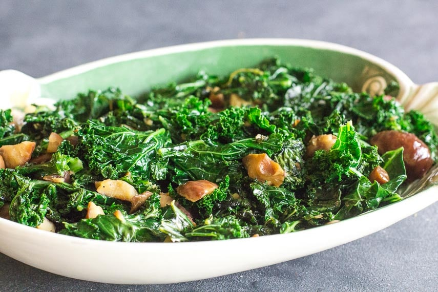 side view of Garlicky Low FODMAP Sautéed Kale with Chestnuts in oval dish