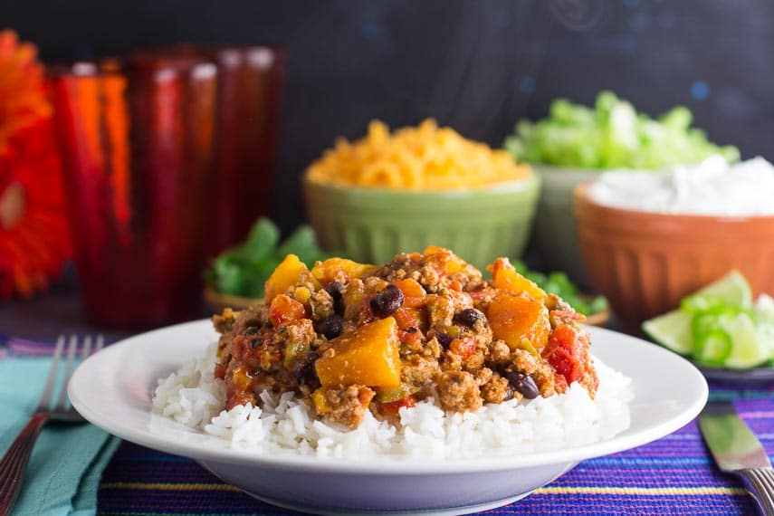 side view of Low FODMAP Turkey Chili with Winter Squash & Beans with rice in a white bowl