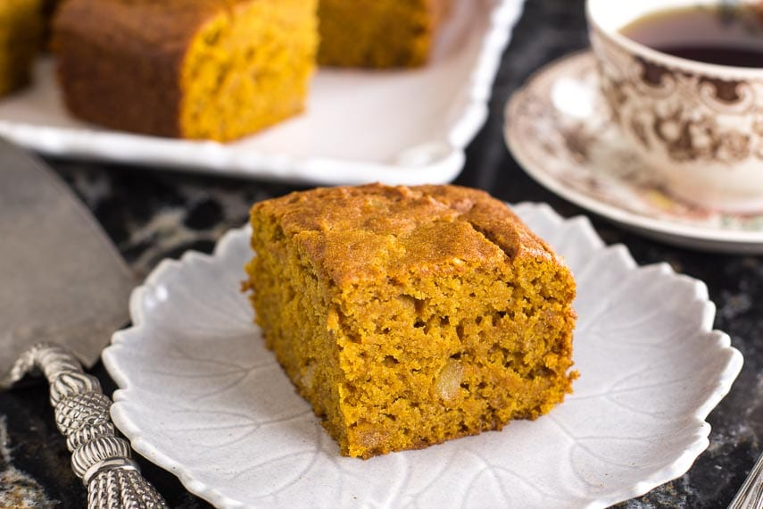 square piece of low FODMAP triple ginger pumpkin cake on white plate; coffee cup in background