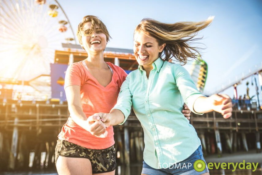 two young women joyfully dancing at a fair
