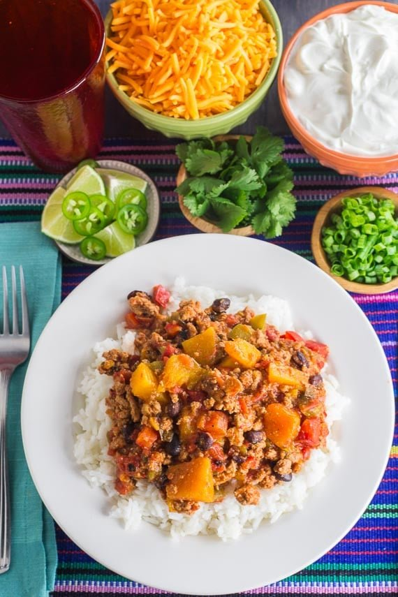 vertical image of Low FODMAP Turkey Chili with Winter Squash & Beans with rice in a white bowl and add-ons like lactose-free sour cream