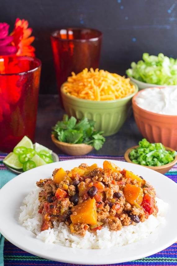 vertical image of Low FODMAP Turkey Chili with Winter Squash & Beans with rice in a white bowl