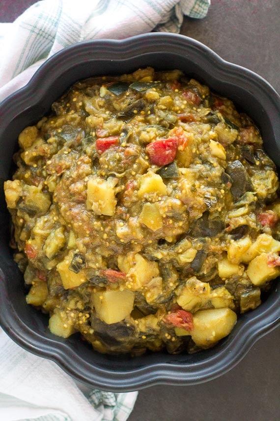 vertical image of Potato eggplant curry in black casserole dish