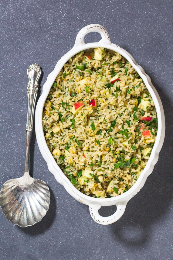 vertical image of Vegan low FODMAP brown rice stuffing with apples & hazelnuts in an oval white casserole on dark surface_