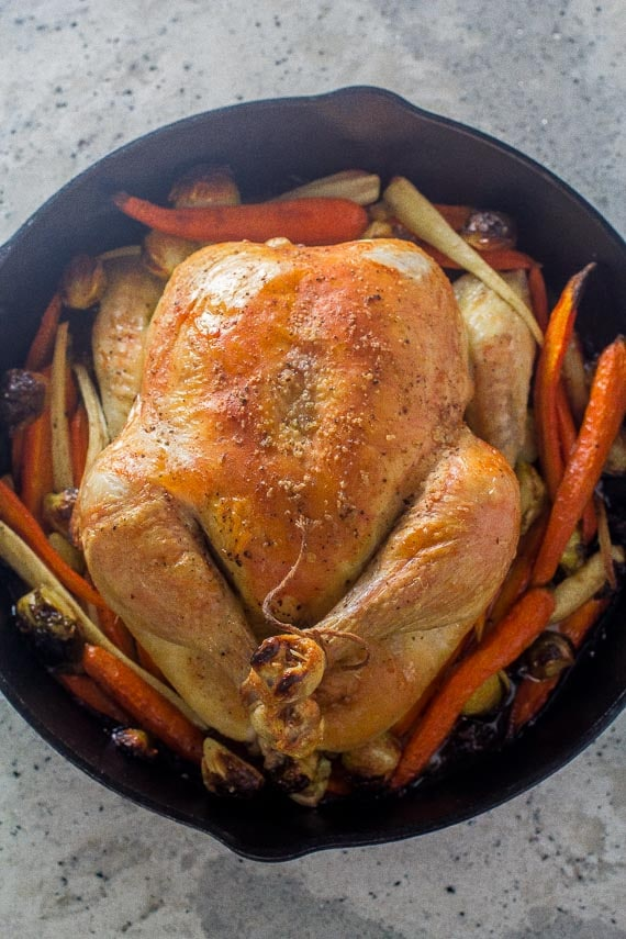 vertical image whole roast chicken and vegetables in cast iron pan on gray quartz