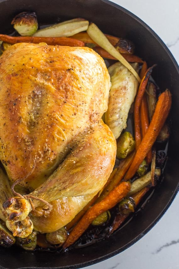 vertical whole roast chicken with vegetables in cast iron pan closeup