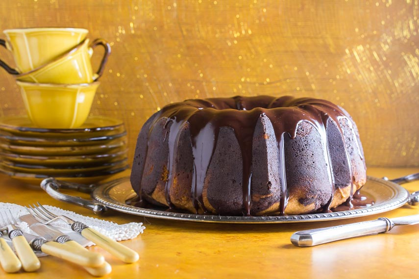 whole low FODMAP Pumpkin Chocolate Marble Cake on silver tray; yellow background