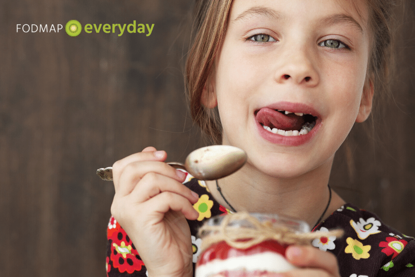 young girl eating yogurt parfait with spoon and licking her lips
