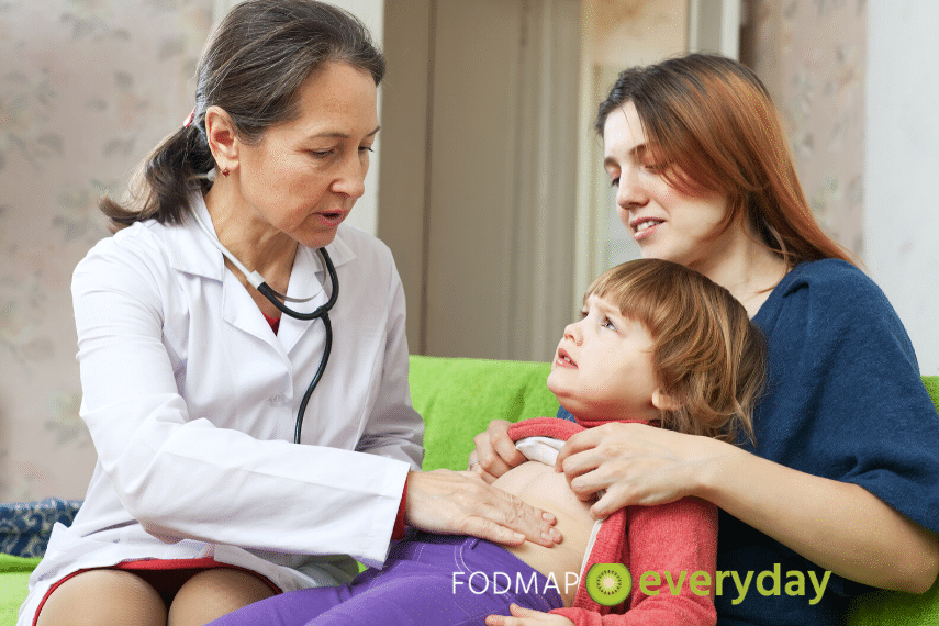 IBS in Children: It's important to obtain a proper diagnosis from a medical doctor. Doctor examining the belly of a young boy sitting in his mother's lap.