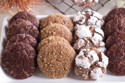 Low FODMAP Chocolate Crinkle Cookies on white platter with various toppings