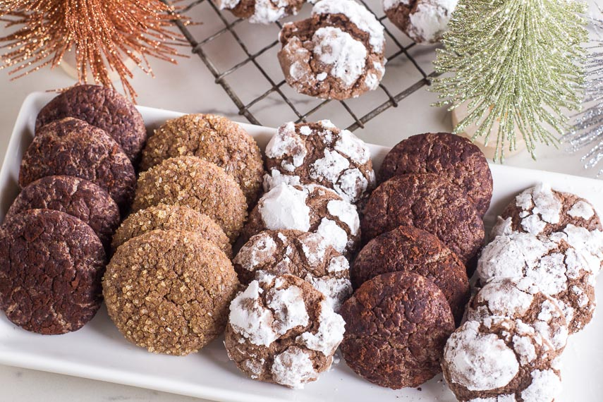 Low FODMAP Chocolate Crinkle Cookies on white platter with various toppings; trees in background