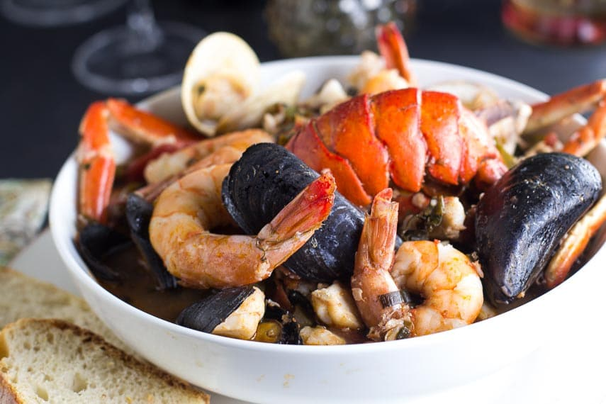 Low FODMAP Cioppino in white bowl with sourdough bread