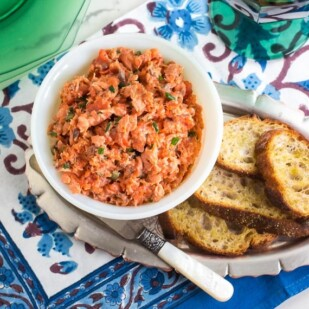 Low FODMAP Salmon Rillettes in white bowl with toasted baguette; pearl handled knife alongside