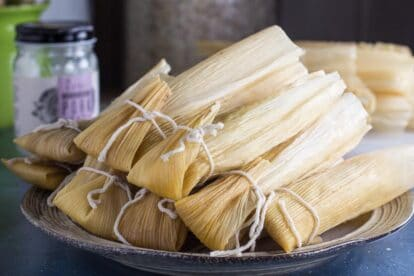 Low FODMAP tamales, piled on plate; jar of lard in background