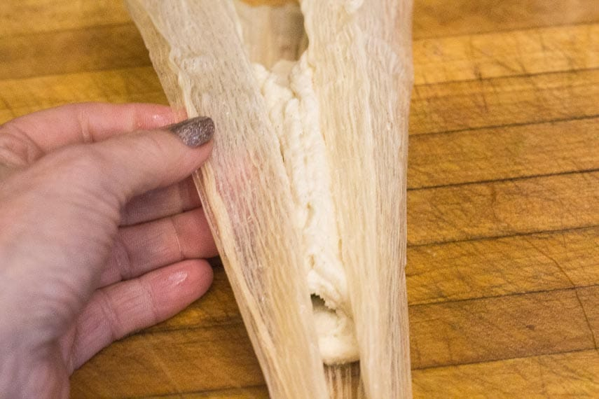 Using cornhusk to encase masa harina around chicken filling in our Low FODMAP tamale