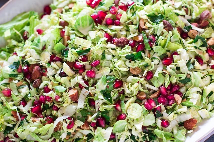closeup of Low FODMAP Brussels sprouts salad with pomegranate and almonds on white oval platter_