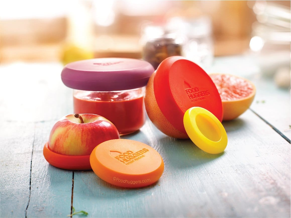 Food hugger product of silicone lids sealing a sliced apple and different containers