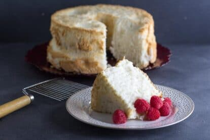 low FODMAP angel food cake in background; slice in foreground. Angel Food Cake cutter alongside
