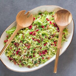 overhead image of Low FODMAP Brussels sprouts salad with pomegranate and almonds on white oval platter on dark surface