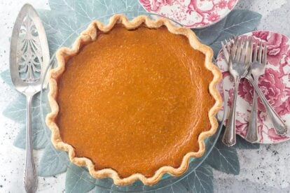 overhead image of low FODMAP classic pumpkin pie in glass pie plate with silver server