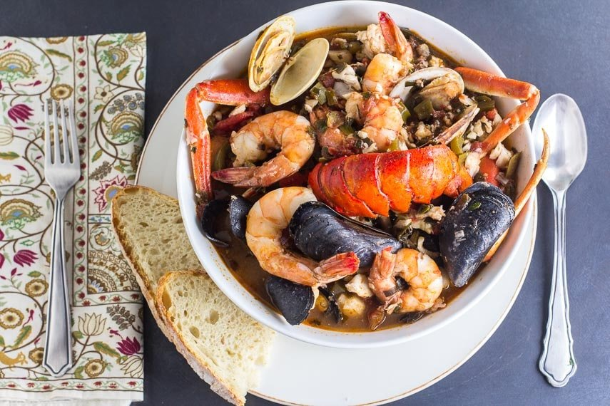 overhead of Low FODMAP Cioppino in white bowl with sourdough bread