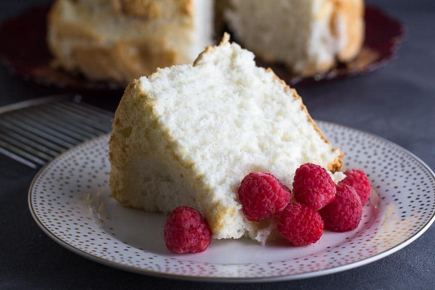 slice of low FODMAP Angel Food Cake on decorative plate with fresh raspberries