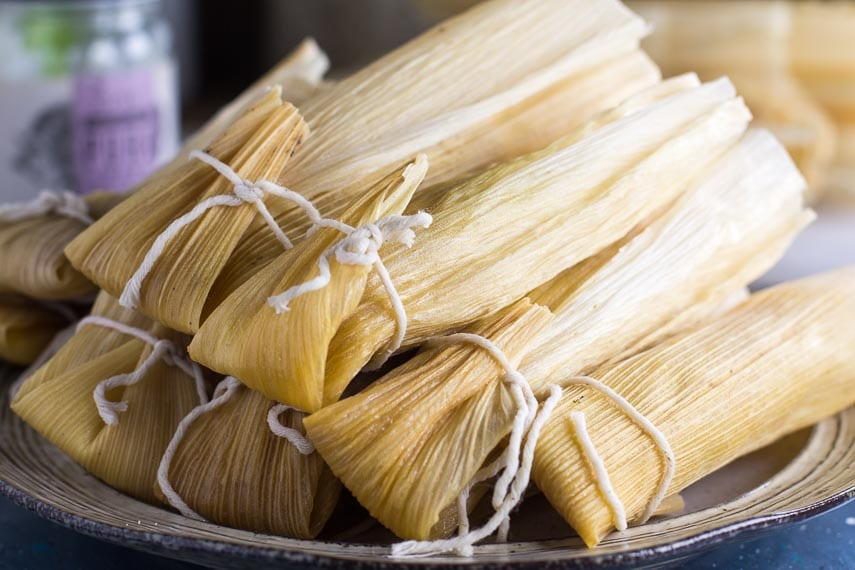 stack of Low FODMAP tamales, piled up on a rustic ceramic dish; tied with Butcher's twine