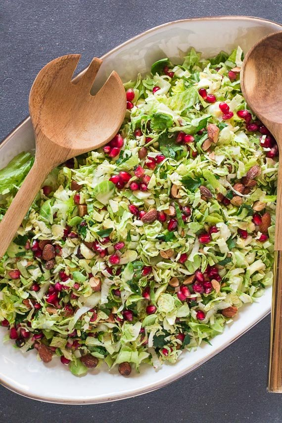 vertical image of Low FODMAP Brussels sprouts salad with pomegranate and almonds on white oval platter on dark surface