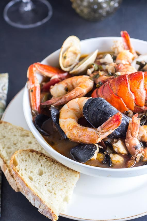 vertical image of low FODMAP Cioppino in white bowl with bread alongside