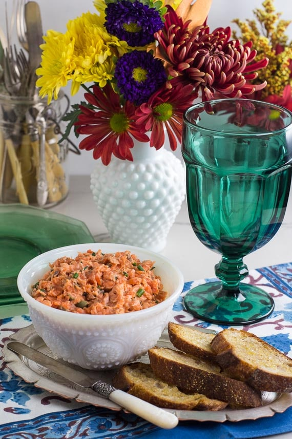 vertical image of low FODMAP Salmon Rillettes in white bowl; teal glass alongside and fresh flowers in white vase