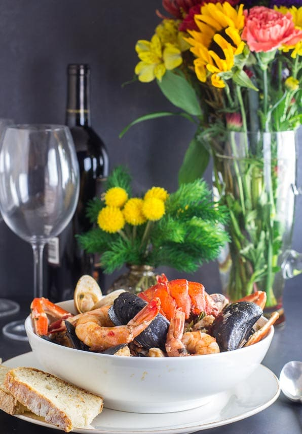 vertical of Low FODMAP Cioppino in white bowl with sourdough bread