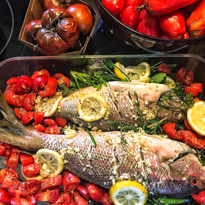 wild snapper, stuffed with fresh herbs in pan