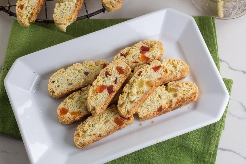 Low FODMAP Tropical Biscotti on white platter with green napkin; cooling on cooling rack in background