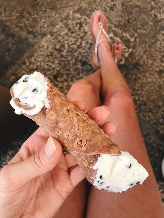 cannoli Sicily style. Cannoli held in woman's hand above bare legs