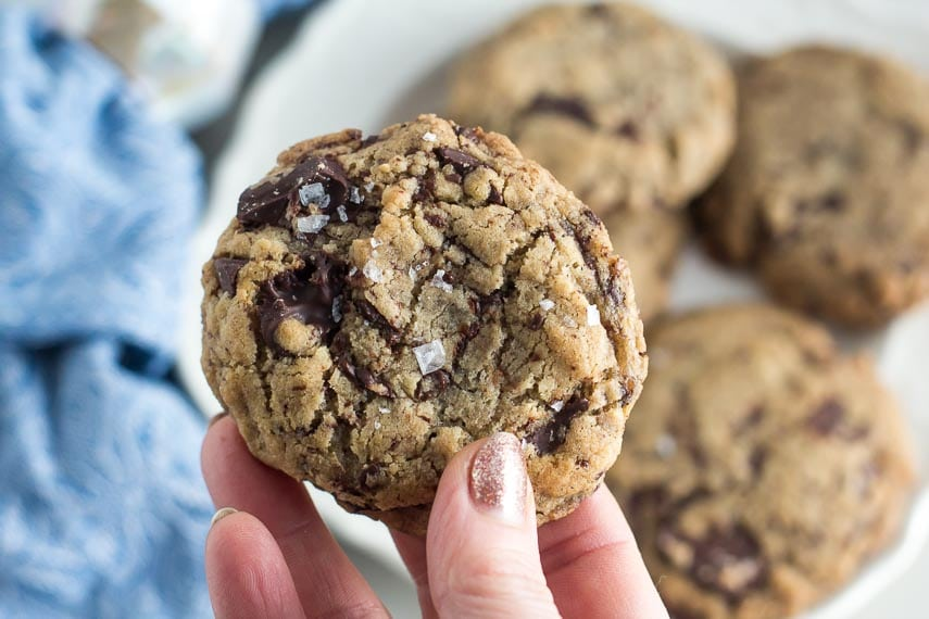 closeup of low FODMAP vegan chocolate chunk cookie sprinkled with salt; held in hand