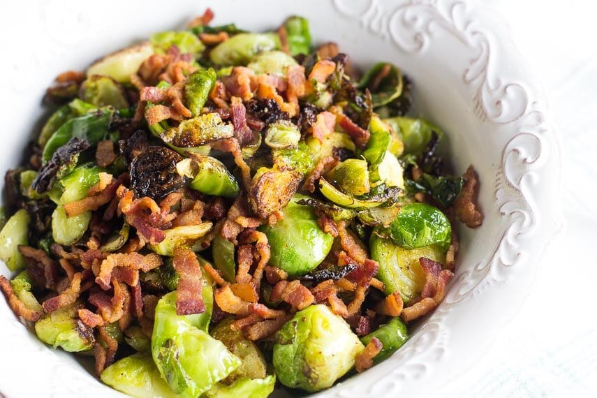 low FODMAP Brussels sprouts and bacon in white dish with raised decorative edge