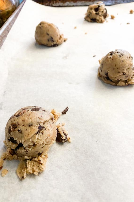 low FODMAP vegan chocolate chunk cookies on baking sheet pan, doled out with scoop for evenly sized cookies